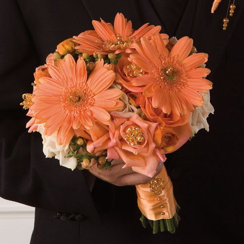 Orange Gerberas berries and orange roses in this hand tied bouquet tied