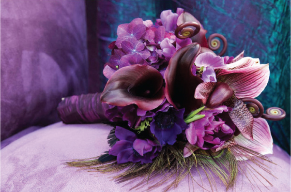 Lush and stunning purple bouquet with peacock feathers