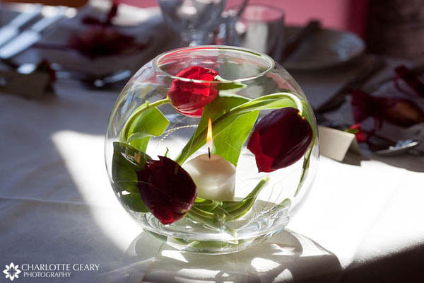 Red tulips and candle in a glass bowl centerpieces