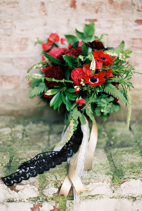 Red bridal bouquet of garden roses, anemones, berries, and greenery
