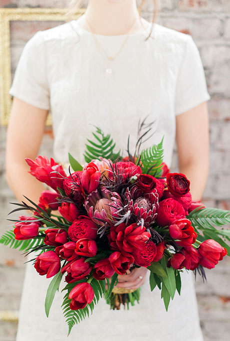 Red bouquet of garden roses, tulips, protea, and ferns