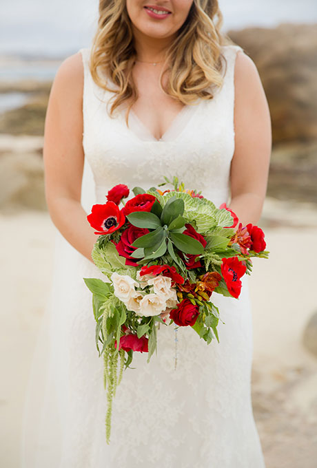 Red bouquet of ranunculus and roses, accented with white blooms and greenery