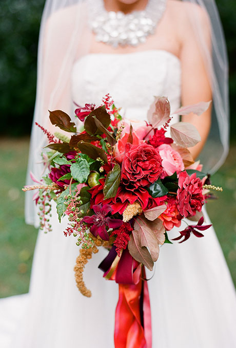 Red roses, clematis, and astilbe accented with colorful greenery