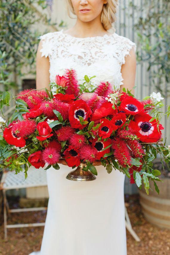 red bopuquet anemones and bottle brish