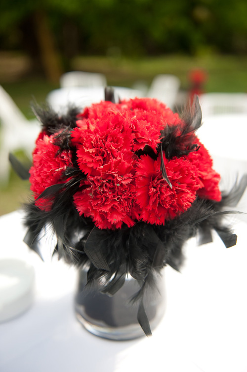 Red carnations and black feathers centerpiece bouquet