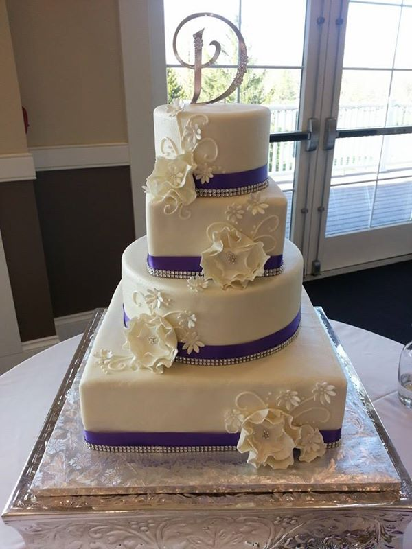 White wedding cake with deep purple satin ribbon